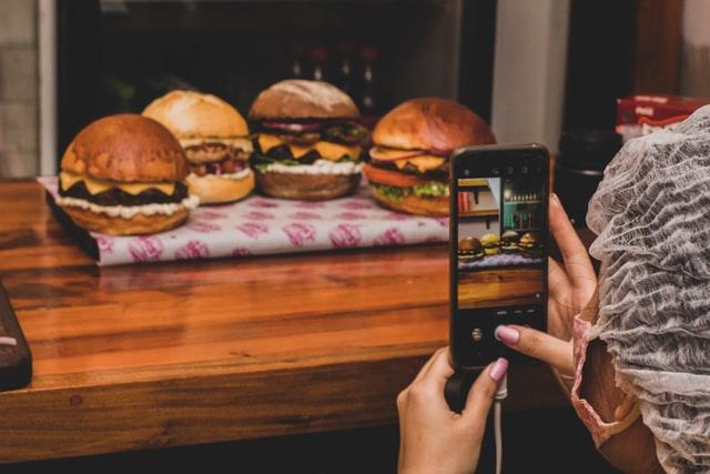 femme qui prend en photo des burgers avec son smartphone